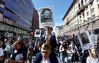 People hold portraits of their relatives who fought in World War II during an Immortal Regiment march on the day of the 73rd anniversary of the Victory over Nazi Germany in the 1941-45 Great Patriotic War, the Eastern Front of World War II, Moscow, May 9