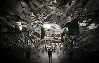 A tourist taking pictures in the entrance way to a shopping mall decorated with mirrors in Tokyo, May 18