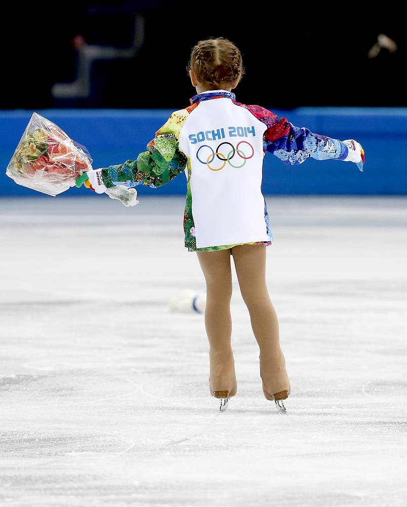 A flower girl collects flowers during the Pairs Short Program of the Figure Skating event