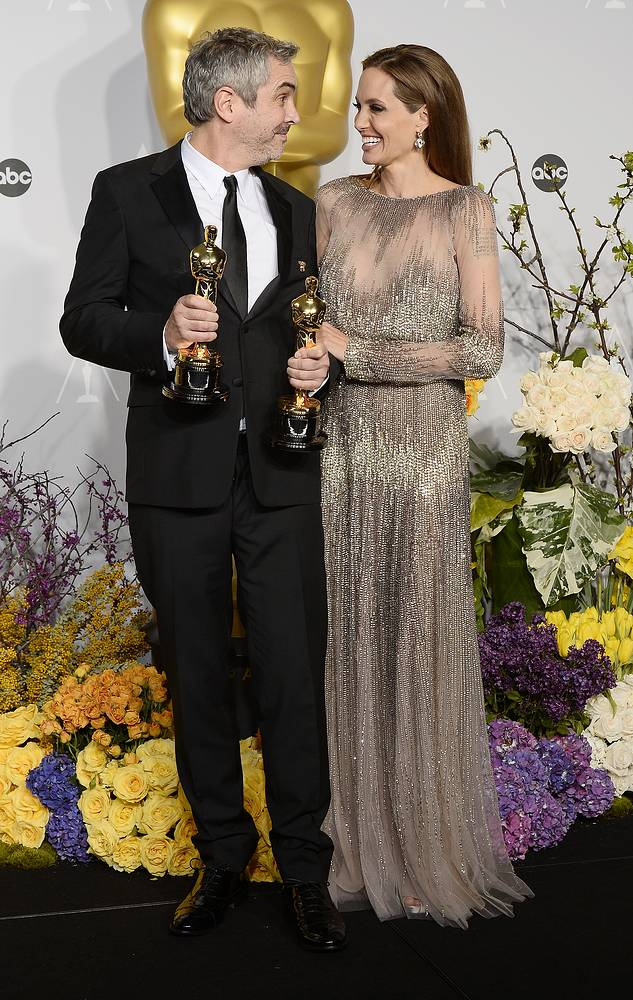Mexican director Alfonso Cuaron (L) holds his Oscars for Best Achievement in Directing and Best Achievement in Film Editing for 'Gravity' as he stands with US actress Angelina Jolie (R)