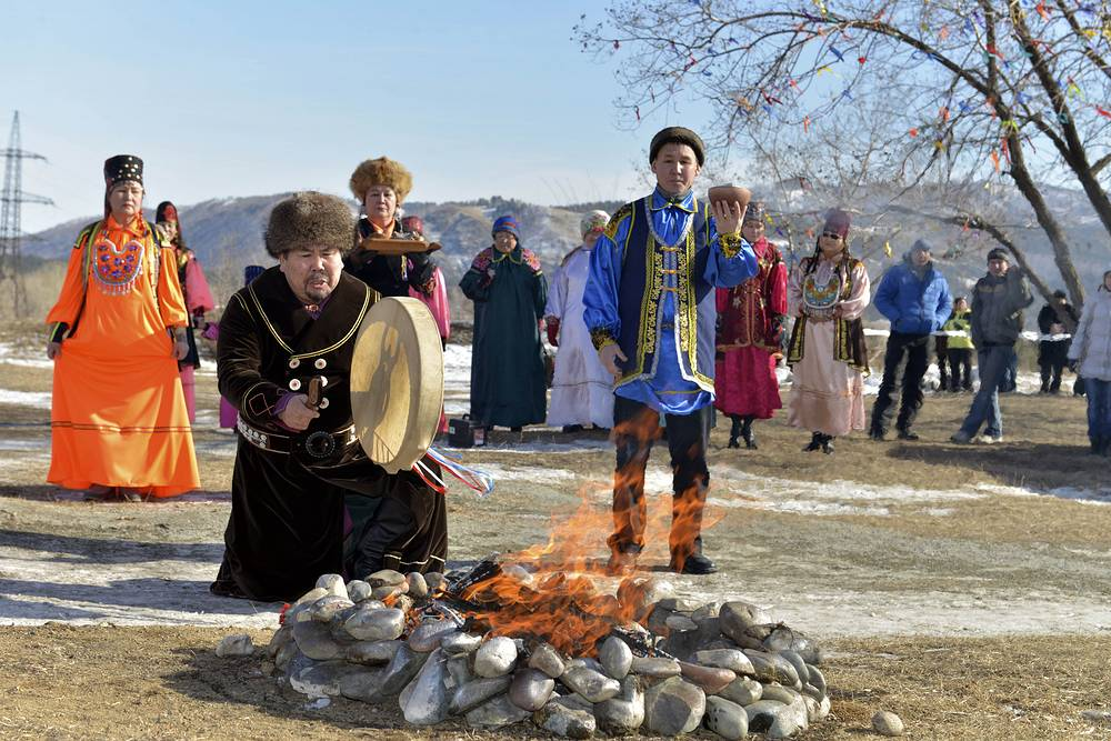 A shaman makes fire to light a Paralympic torch at a special ceremony during the Paralympic torch relay in Sayanogorsk