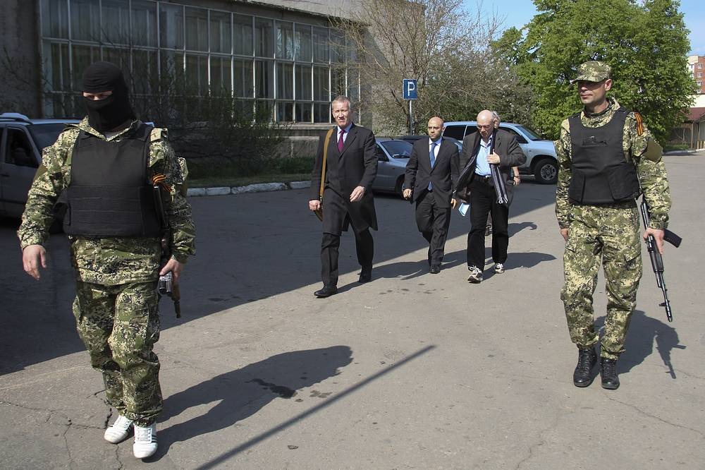 A group of Organization of Security and Cooperation in Europe (OSCE) delegates are escorted by pro-Russian militants as they arrive to attempt to negotiate the release of a group of foreign military observers