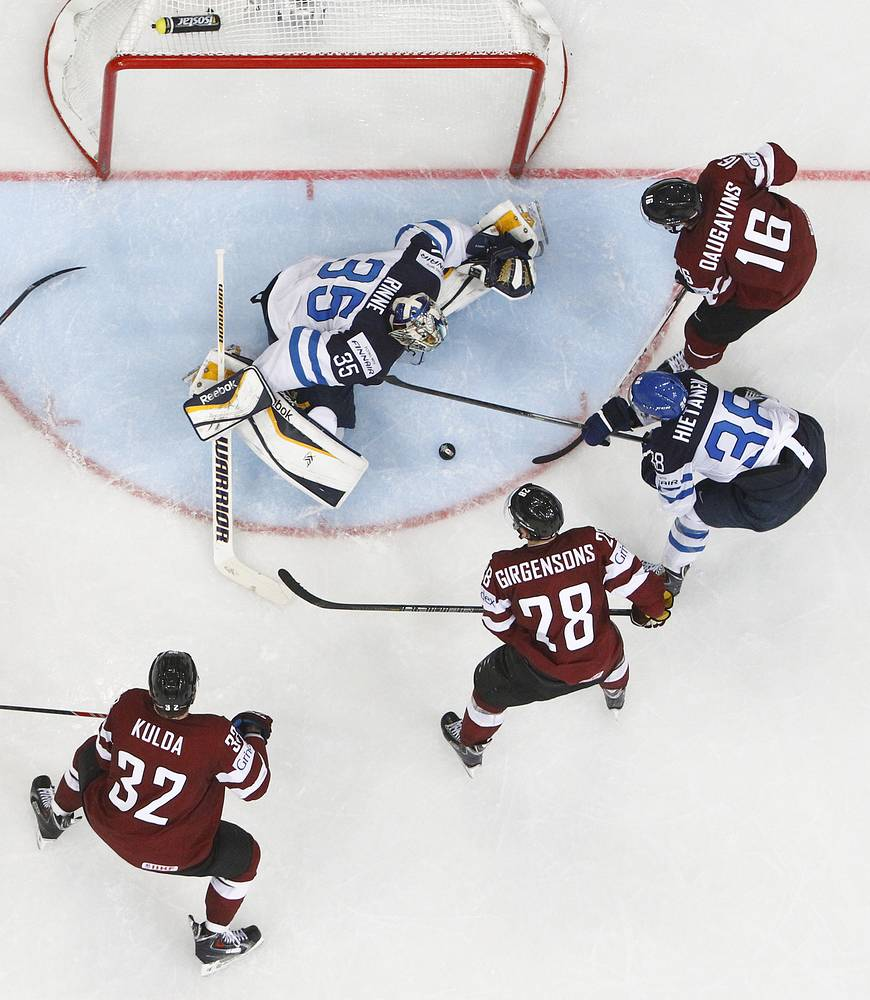 Finland's goalie Pekka Rinne (background) in action in the Group B ice hockey match against Latvia