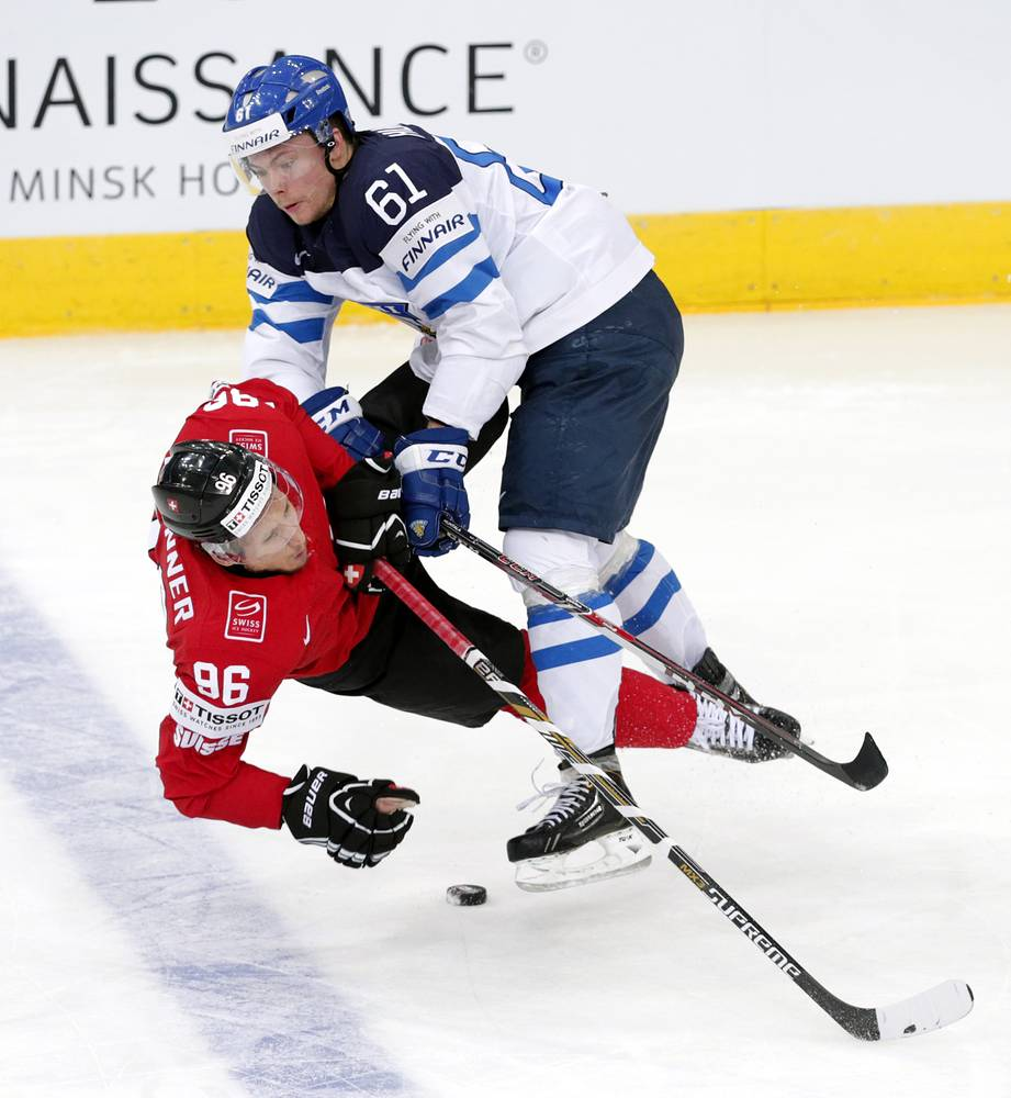 Tommi Huhtala (R) of Finland in action against Swiss player Damien Brunner