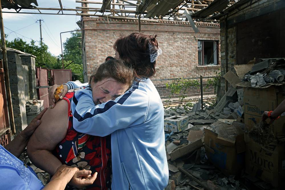 Owner of a house damaged by shelling being comforted