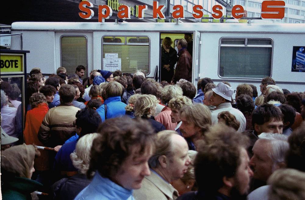"""East German citizens crowd a mobile bank office in West Berlin to pick up """"welcome money"""" donated by the West Germany government for East Germans visiting the West"""
