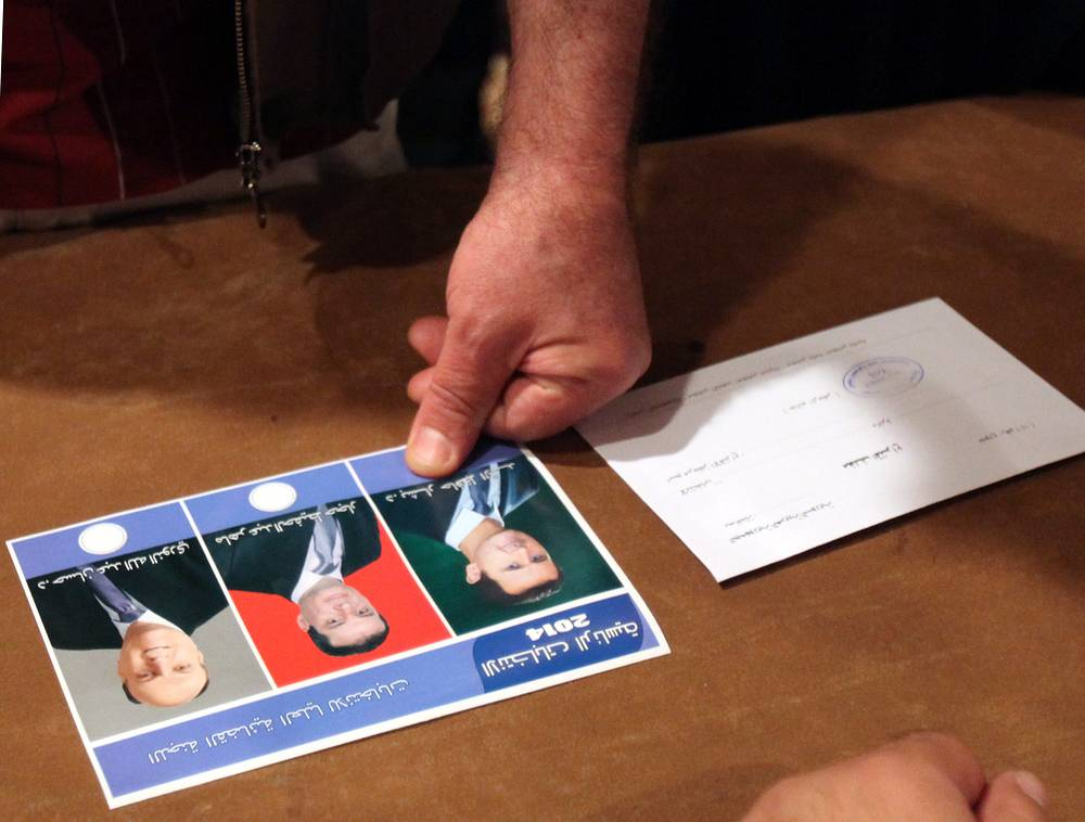 A voter marks the election card with his own blood in a show of loyalty for incumbent Syrian President Bashar Assad