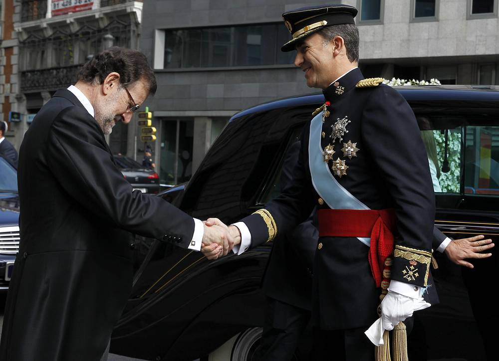Spain's new King Felipe VI (R) is welcomed by Prime Minister Mariano Rajoy