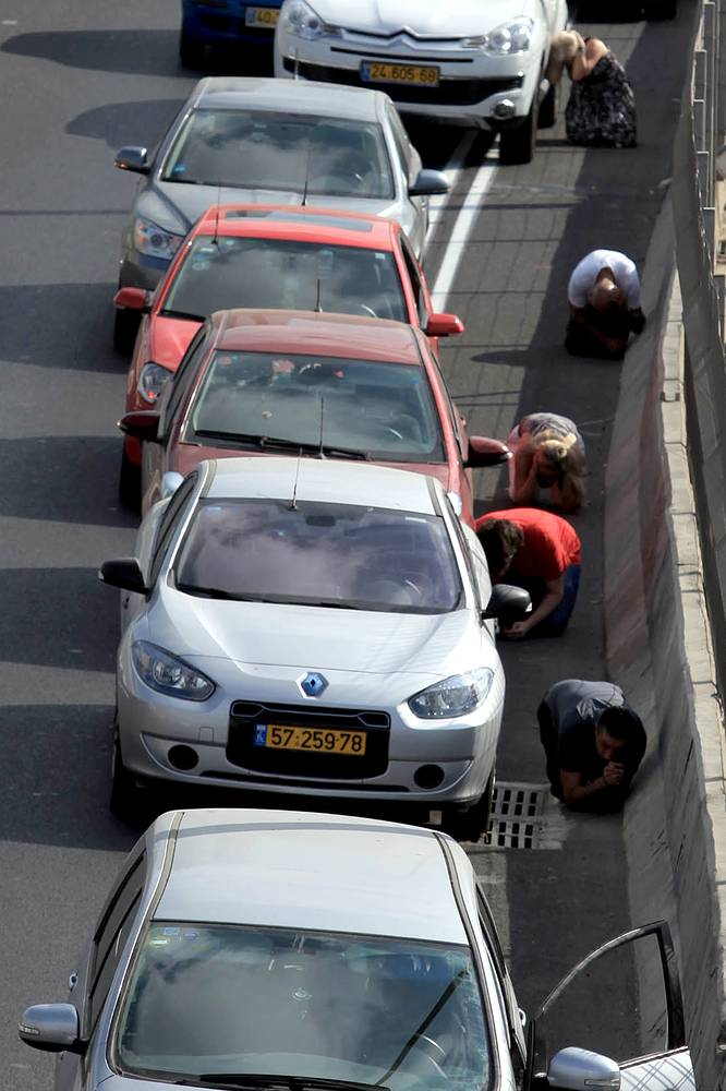 Israelis lay on the ground and take cover near their cars while sirens sound over the city of Tel Aviv