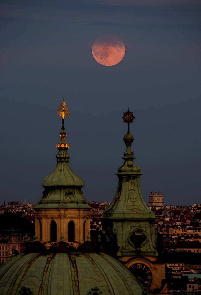 Supermoon rises over the St Nicholas Church in central Prague, Czech Republic