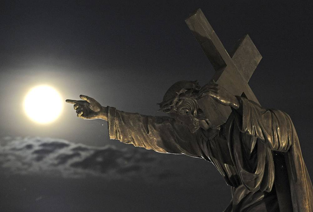 A supermoon rises above a Jesus Christ statue in front of the Holy Cross church in Warsaw, Poland
