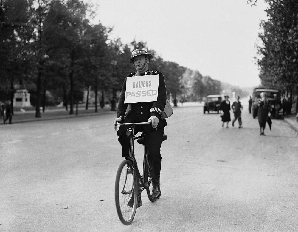A policeman rides a bicycle announcing the end of the first air-raid warning in London on September 3, 1939