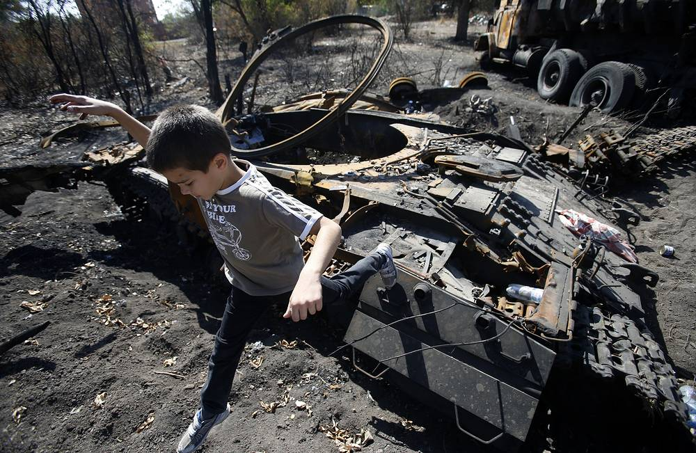 Locals examine destroyed hardware of the Ukrainian government forces