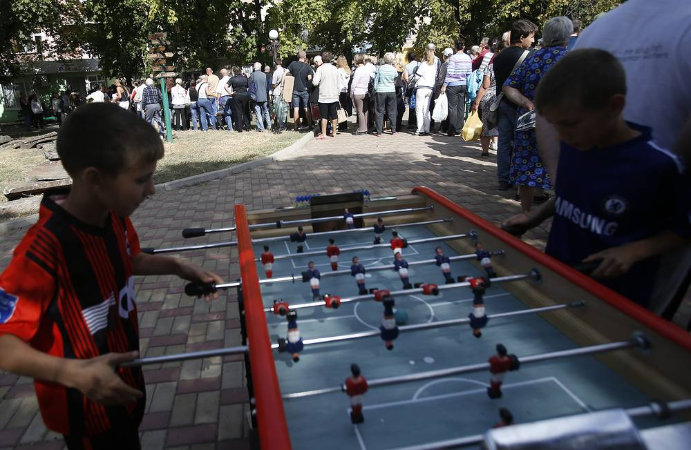 Residents wait in line for food and water as children play a table soccer game in the city of Luhansk