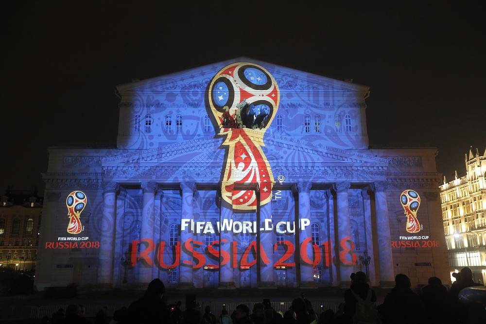 Emblem was demonstrated on the Bolshoi Theatre building in Moscow. It features space flights, icon painting techniques, love for football