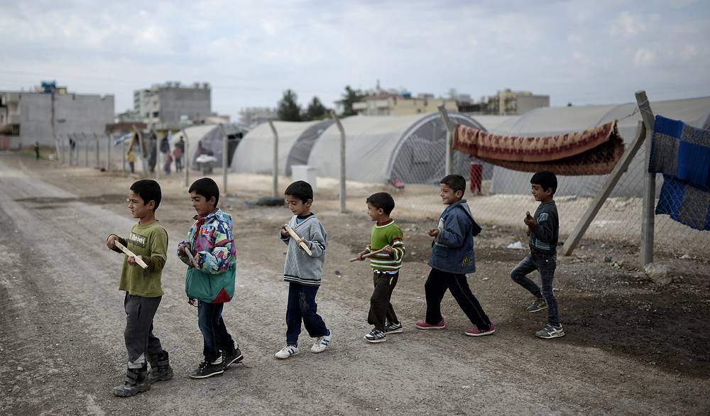 Photo: Syrian refugee children who fled from Kobane, Syria, play acting as fighters at a refugee camp in Suruc district, Sanliurfa, Turkey, 28 October 2014