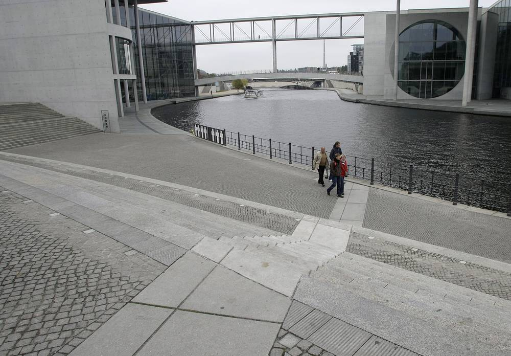 Photo: Tourists cross the Berlin Wall Trail in the government district in Berlin, Germany. The stones mark the spot, where the Berlin Wall used to stand