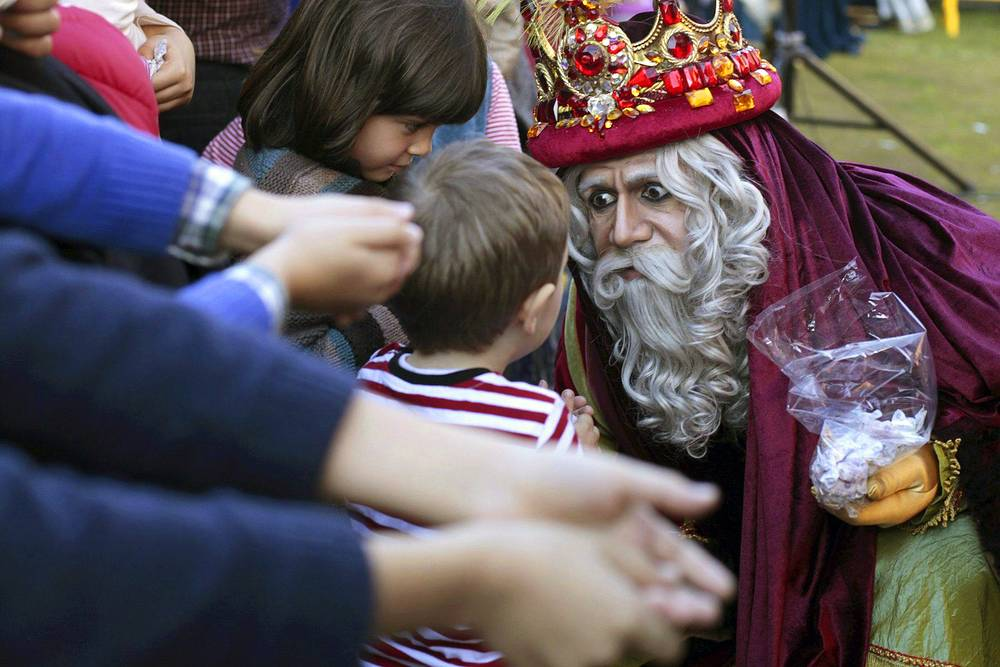 In Spain and Spanish-speaking parts of the world, Three Wise Men are traditionally in charge of bringing presents to children. Photo: King Melchior, one of the Three Wise Men (or Three Kings), greets children in Tenerife, Canary Islands, Spain. On the Epiphany (January 6), the Catholic Church marks the visit of the Three Kings to the baby Jesus in Bethlehem