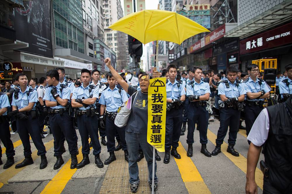 A lone pro-democracy demonstrator carries a yellow umbrella and chants slogans in front of a line of policemen in Mongkok, Hong Kong