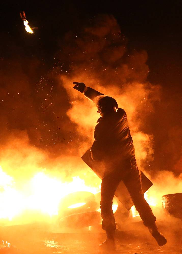 A protester throws a Molotov cocktail during riots in Kiev