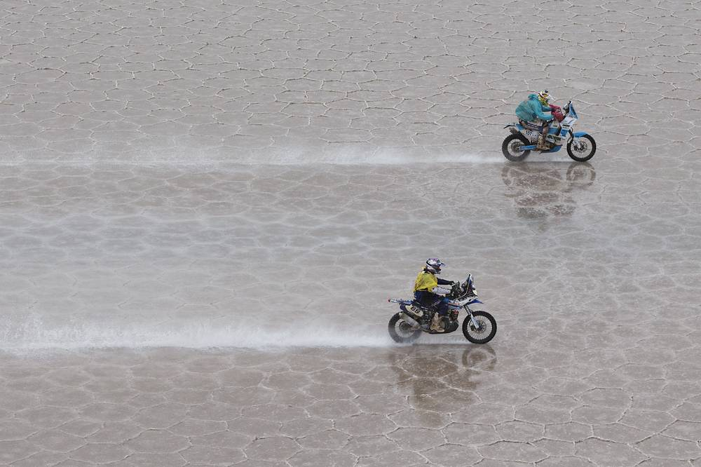 Yamaha rider Hugo Payen of France, bottom, and KTM rider Milan Engel of Czech Republic, race across the Uyuni salts flat during the 8th stage of the Dakar Rally 2015 between Uyuni, Bolivia, and Iquique, Chile, January 12