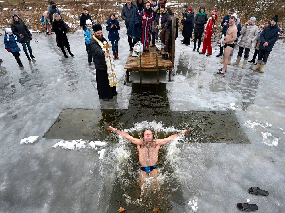 Believers traditionally plunge into cold water on Epiphany. Photo: Celebrations of the Orthodox Epiphany outside Zaslavl town, Minsk region, Belarus