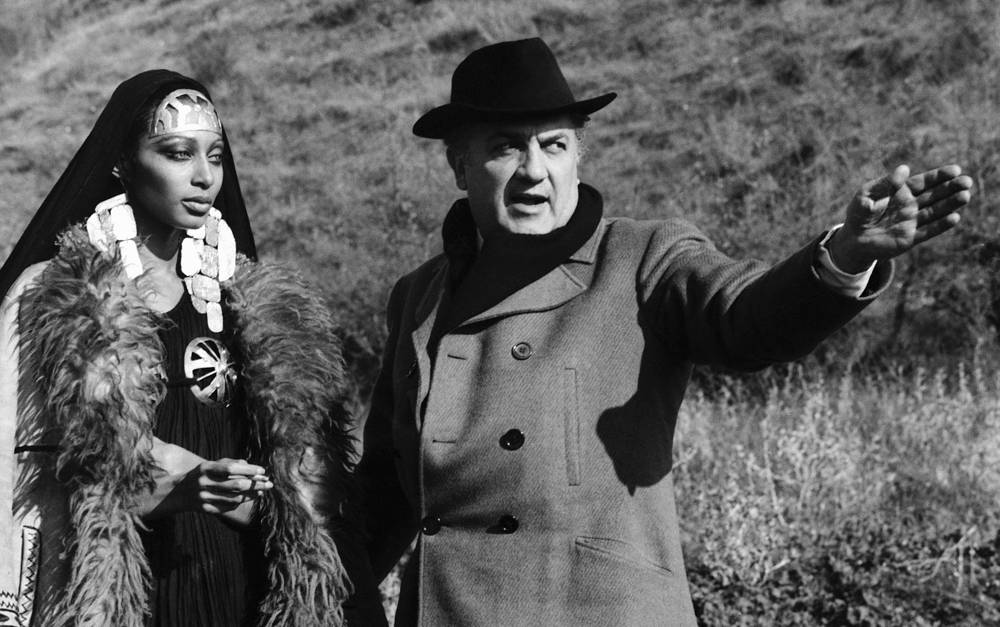Italian director Federico Fellini  and American fashion actress Donyale Luna on the set of the film Satyricon, 1968 for which he got Academy Award nomination for Best Director
