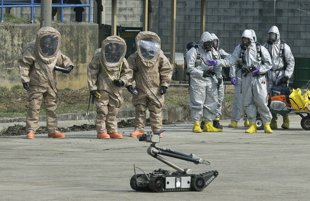 US Army soldiers watch a bomb disposal robot during a demonstration of their equipment