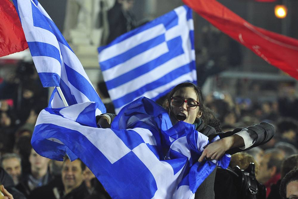 Photo: A woman waving a Greek flag during a speech by the leader of Syriza left-wing party Alexis Tsipras