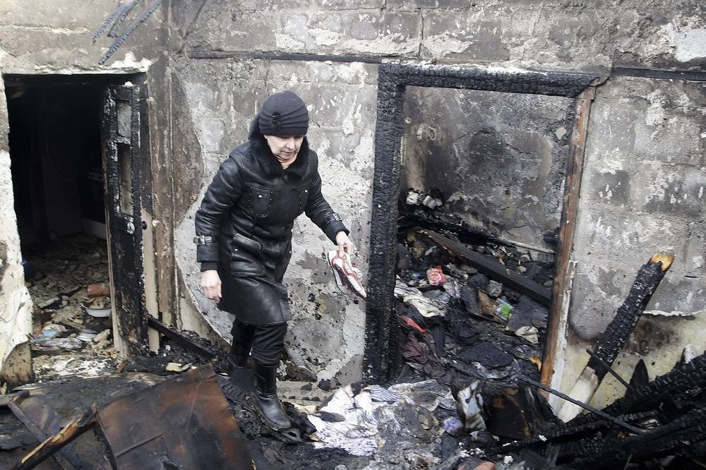 OSCE mission in Ukraine says crisis is deteriorating and urges ceasefire. Photo: A woman inspects her damaged home after shelling in Donetsk