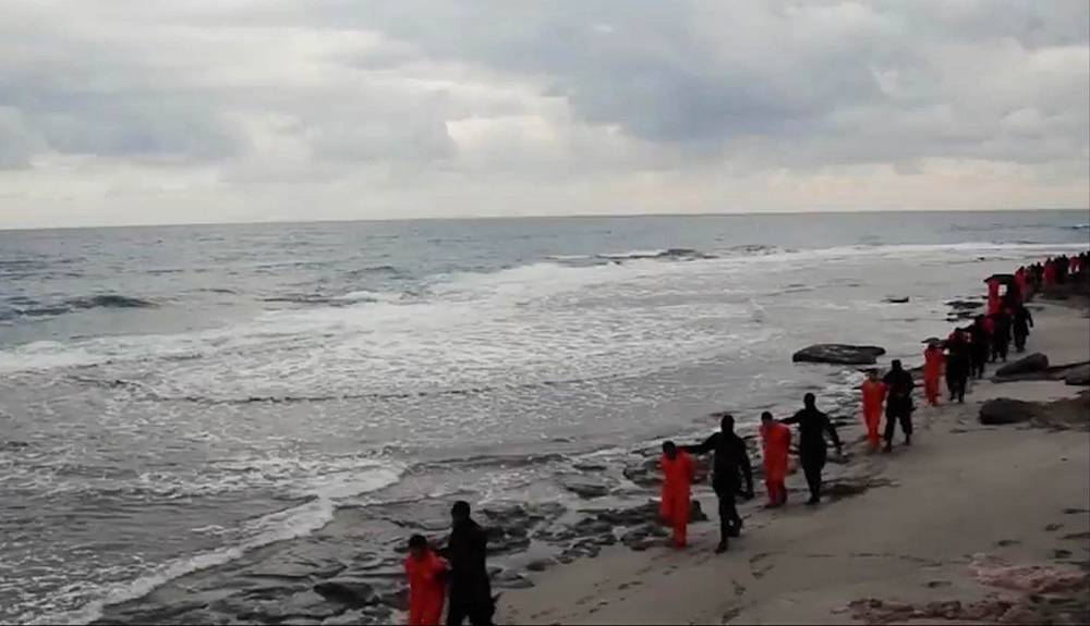 Egyptian Coptic Christians in orange jumpsuits being led by Islamic State militants along a beach in Libya. On February 15, 2015 IS militants published a video showing the apparent beheadings of 21 Copts, who were captured by IS at the end of last year