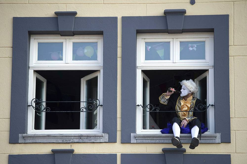 A reveler wearing a colorful costume watches a carnival parade pass by from a window in Roermond, The Netherlands