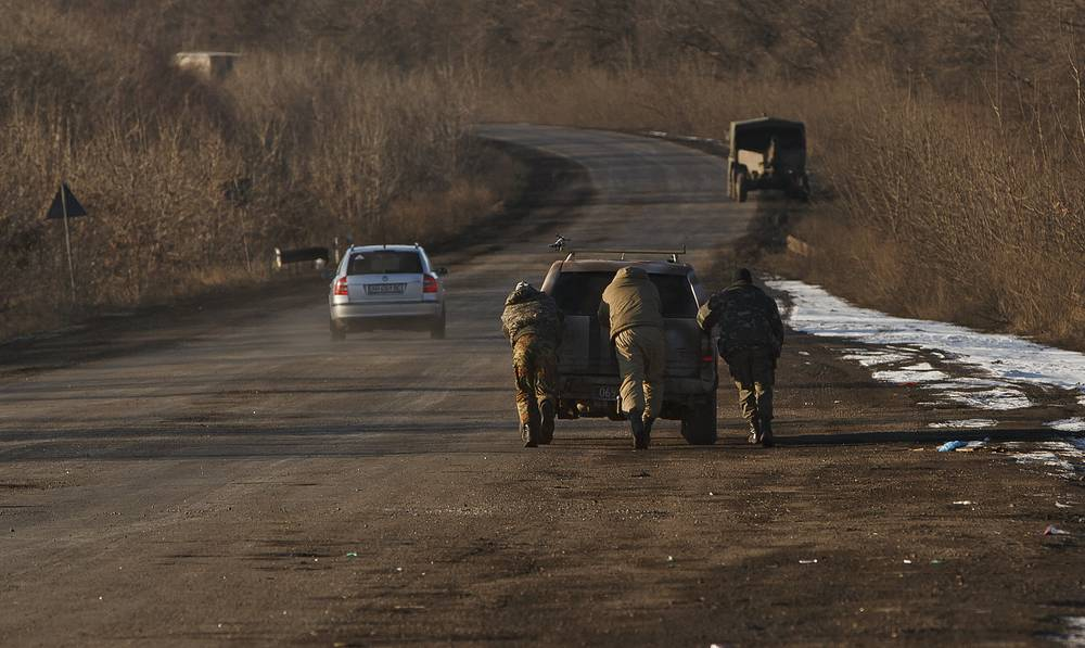 "The head of Donetsk People's republic stated that a section of the Debaltsevo-Artyomovsk highway in the Logvinovo area has become a ""death road"" for Ukrainian troops who attempted to break through the encirclement. Photo: Ukrainian troops push a car as attempt to start it, outside Artyomovsk, Ukraine, while pulling out of Debaltsevo"
