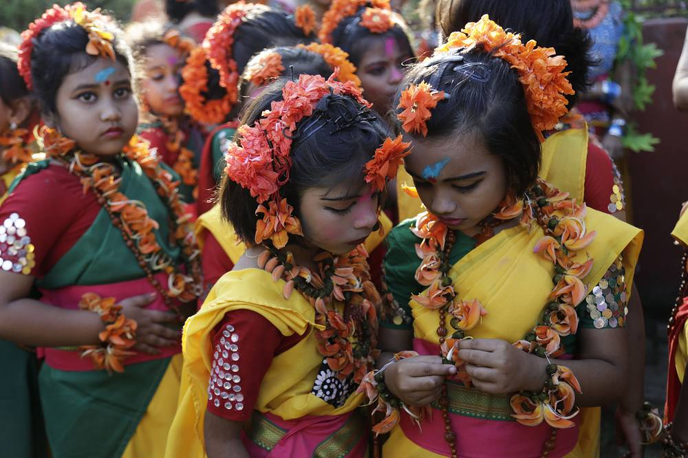 Indian girls decorated with flowers waiting to perform during Holi celebrations in Kolkata, India