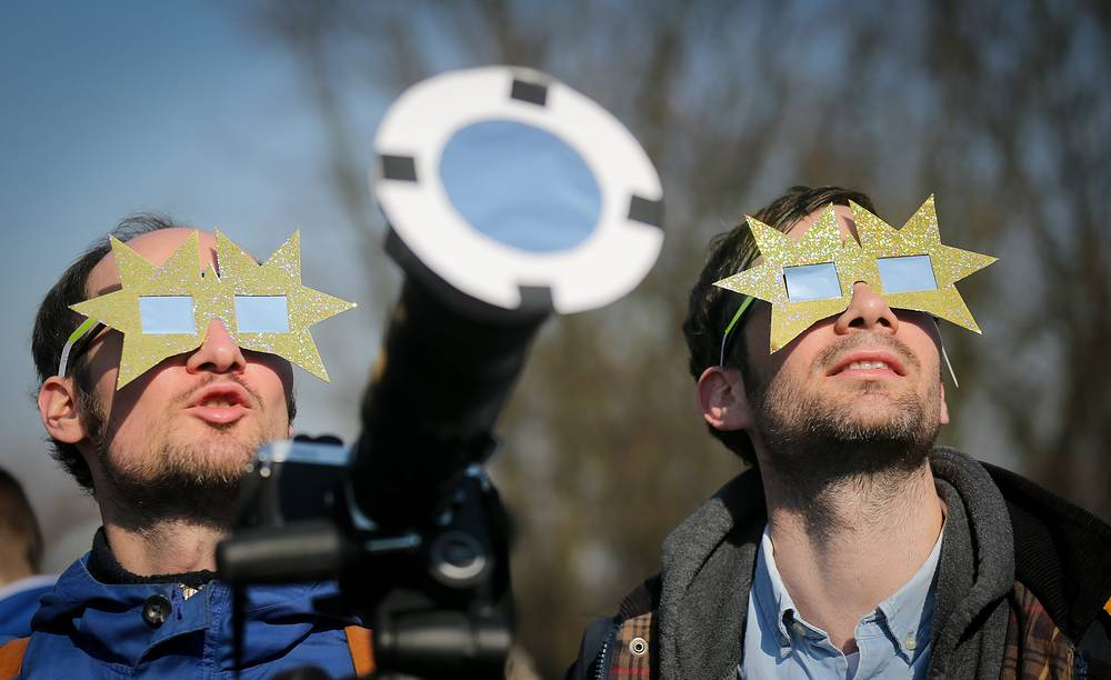 Hobby astronomers gazing with special sunglasses at the partial solar eclipse in front of the observatory in Berlin, Germany