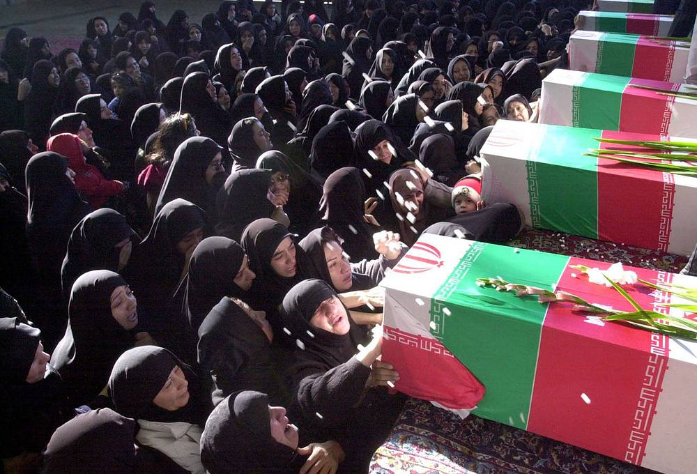 Iranian military aircraft Il-76 crashed on 19 February 2003, killing over 250 members of the elite Revolutionary Guard, and 18 crew, in the Sirch mountains, 32 kms from it's destination Kerman, Iran. Photo: Relatives near the coffins of victims of a plane crash at the funeral ceremony in Tehran