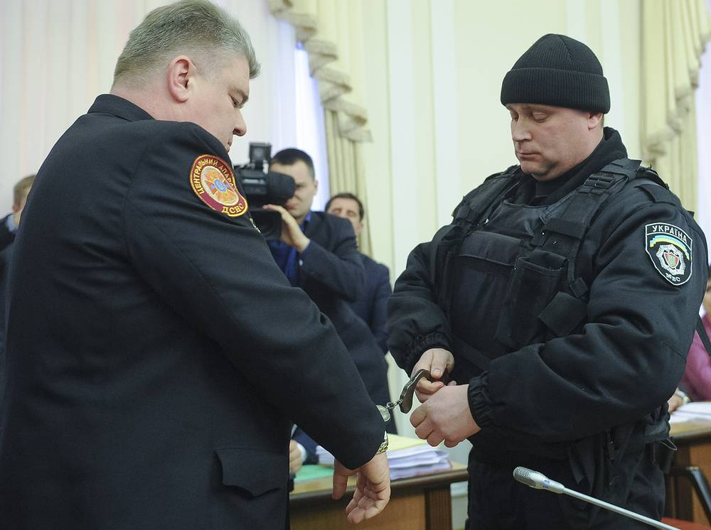 A policeman handcuffs the chief of Ukraine's state service for emergency situations