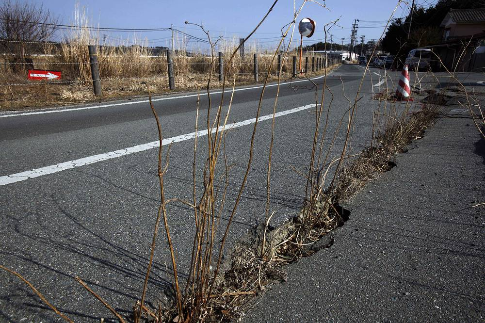 Earthquake-damaged road in the abandoned town of Naraha, which was once inside the nuclear exclusion zone surrounding the Fukushima Dai-ichi nuclear plant, in Japan