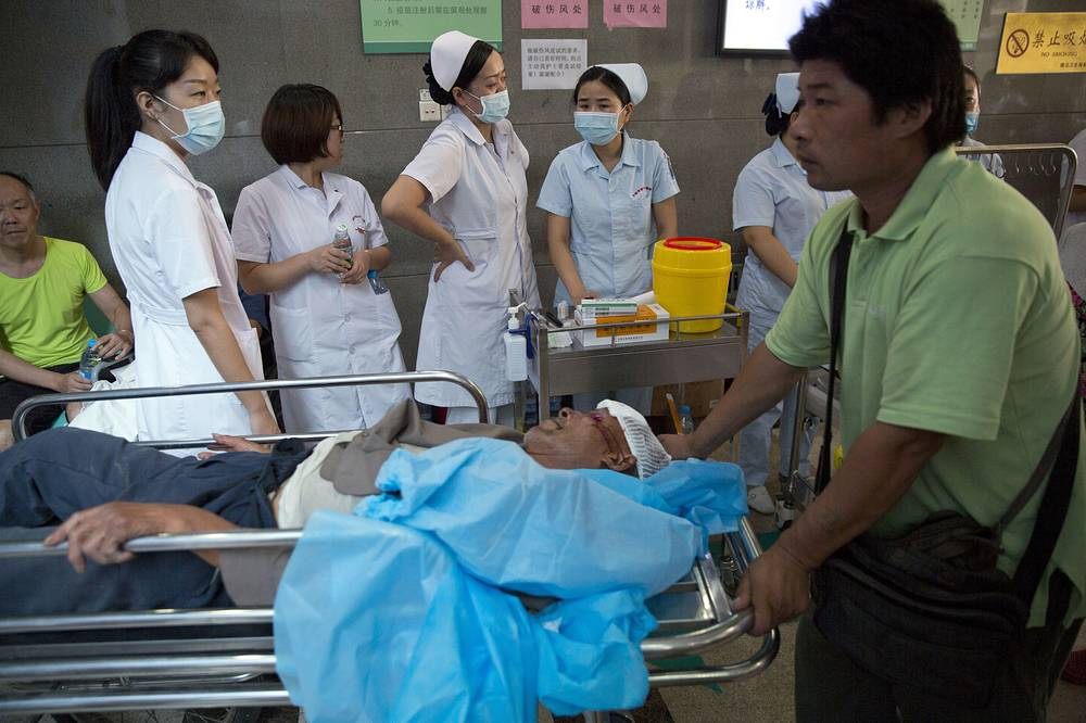 A man pushed through an emergency ward at a hospital receiving victims of an explosion in northeastern China's Tianjin municipality