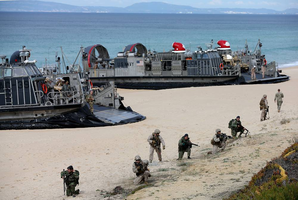 US marines and portuguese fuzileiros lining up to secure US Navy hovercrafts after landing