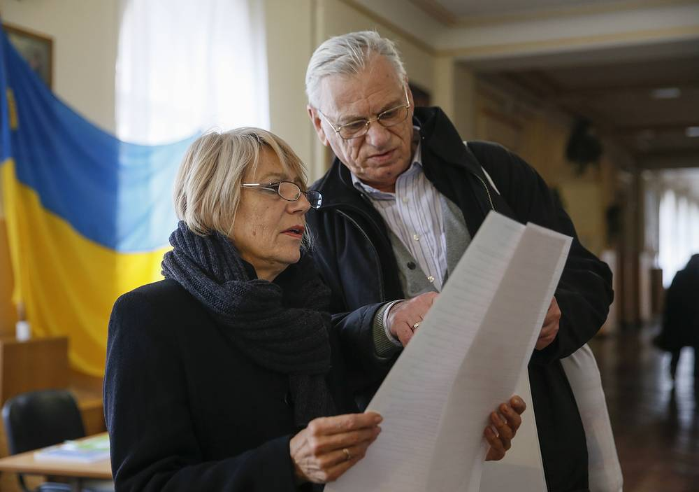 Ukrainians inspecting their ballot papers at a polling station during Ukrainian local elections in Kiev