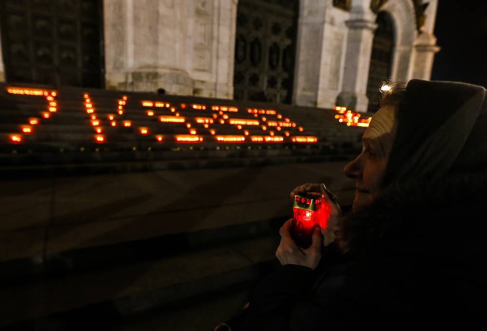 Woman lighting candle in front of candles in shape of number of crashed plane near the Cathedral of Christ the Saviour in Moscow, Russia