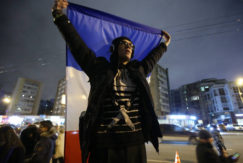 A young man with a French flag outside the French Embassy in Moscow, Russia