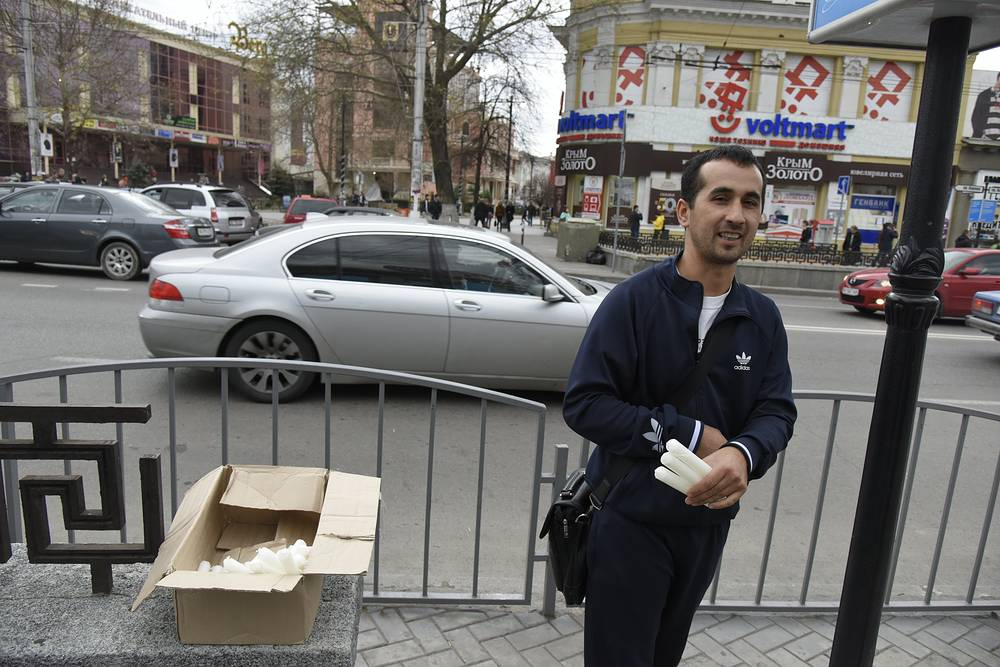 Man selling candles on a street after a power failure, in Simferopol