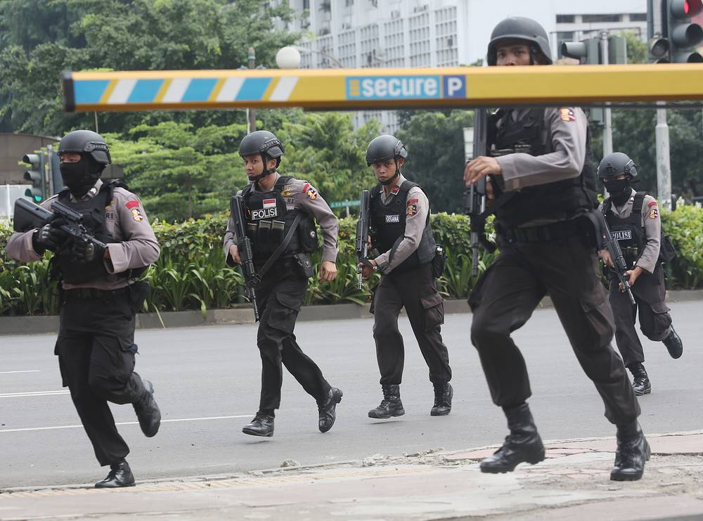 Police officers rushing to take their position near the site of an explosion in Jakarta