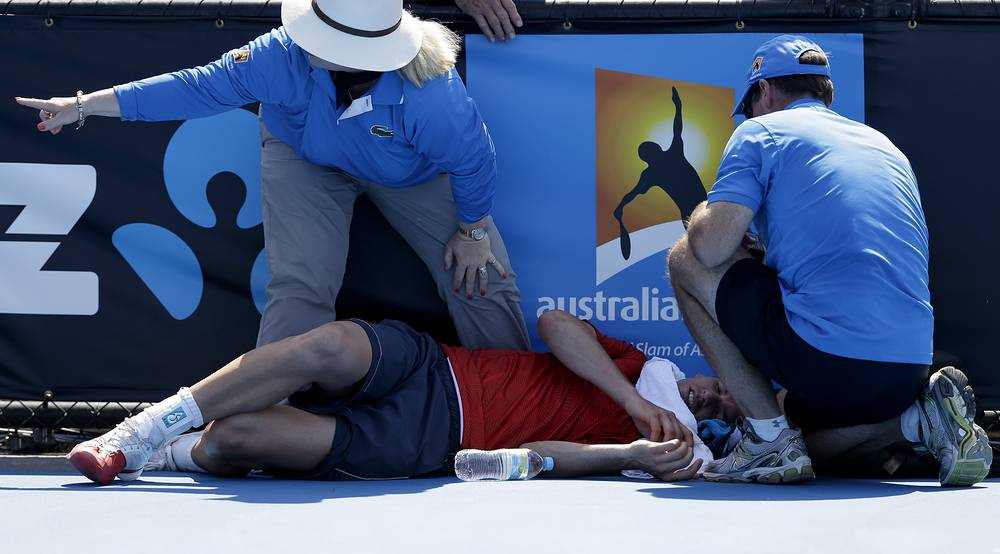 Frank Dancevic of Canada lying on the court after collapsing during his first round match against Benoit Paire of France as temperatures topped at 43 C (108 F) at the Australian Open tennis championship in 2014