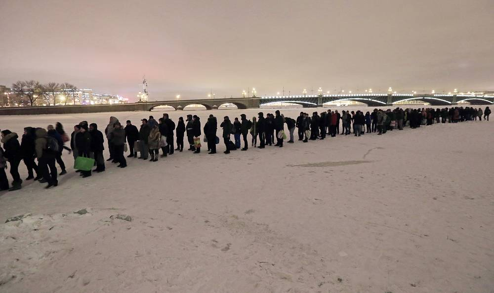 Orthodox believers queue to take a dip in the icy waters of the Neva River, during the celebration of Epiphany in Saint Petersburg