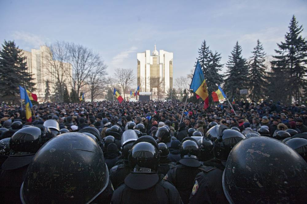 Police guarding the entrance to the parliament building during a protest in Chisinau