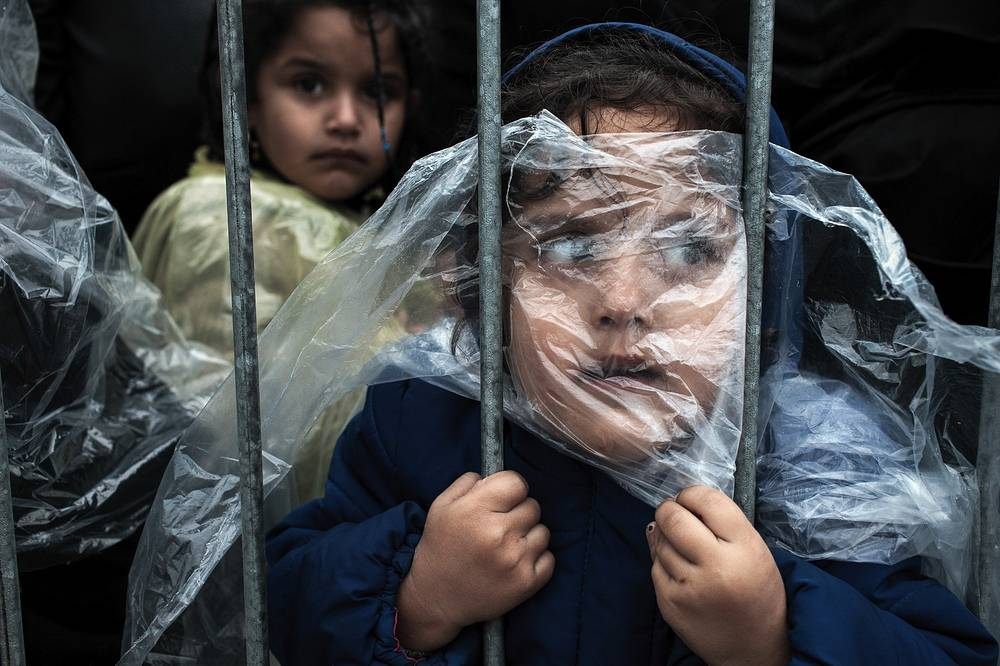 Slovenian photographer Matic Zorman, 1st prize singles in the People category. The picture shows a child covered with a raincoat while she waits in line to register at a refugee camp in Presevo, Serbia, 07 October 2015