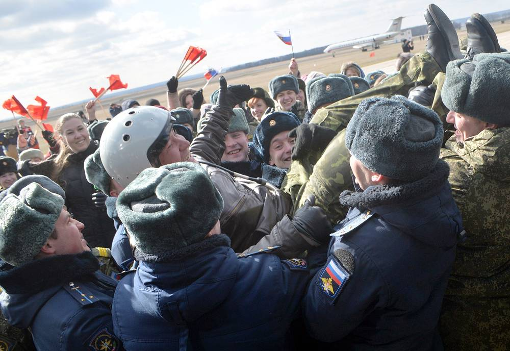 Russian military officers lift up a Russian Aerospace Force pilot during the arrival ceremony in Voronezh Region as the first group of Russian Sukhoi Su-34 fighter bombers return from Syria